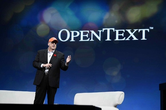 CEO Mark Barrenechea standing in front of a backdrop with the OpenText logo on it.