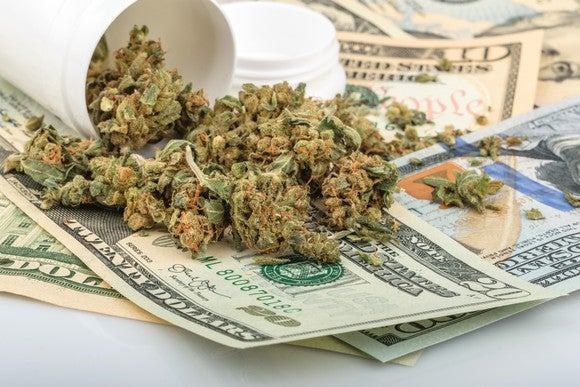A jar of dried cannabis buds lying on a messy pile of cash.