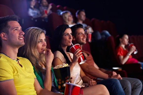 An audience in a dark movie theater eating popcorn and drinking soda.