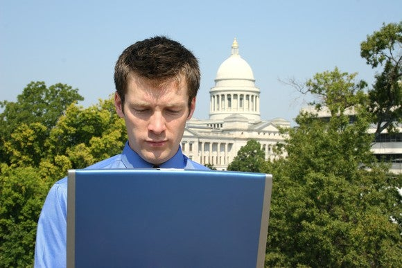 A person on a laptop with the U.S. Capitol building in the background.