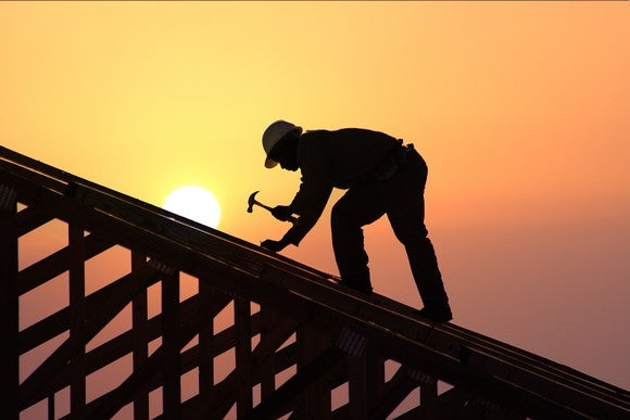 A builder working on the roof of a new home under construction