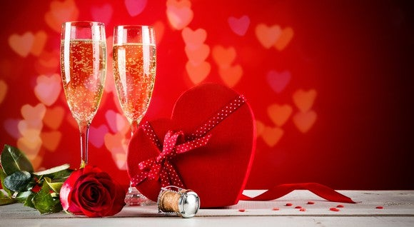 A display of champagne glasses, a rose, and a box of chocolates.