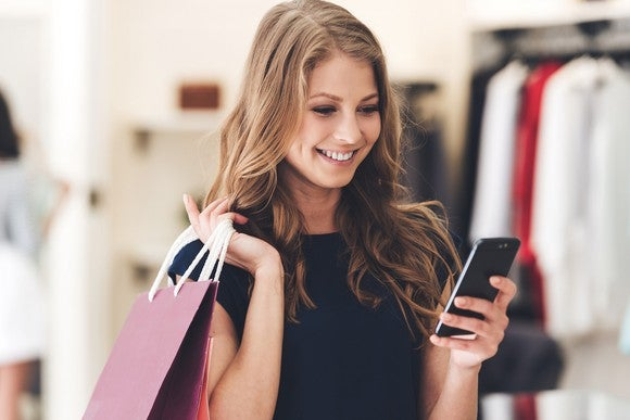 Smiling young woman shops while looking at her smartphone.