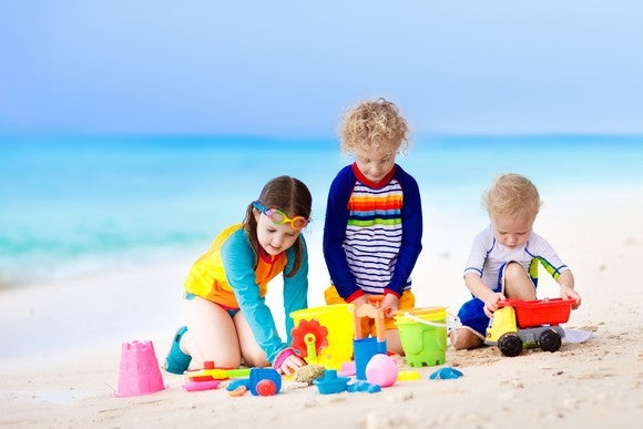 Kids playing with toys at the beach.