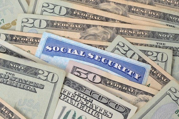Social Security card embedded within a spread-out pile of cash.