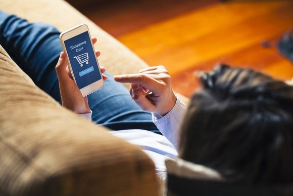 A person shopping on their phone while lying on a couch.