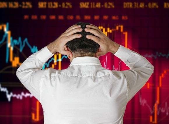 A man looks at a screen of stock chart performance with hands on his head in frustration.