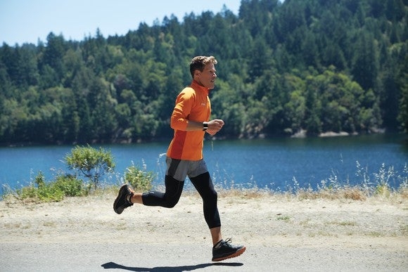 Man wearing a Fitbit and running along a lake with trees in the background.
