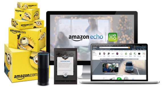 A stack of boxes, an Amazon Echo, a tablet, a desktop, and a laptop featuring images of Amazon's ad products.
