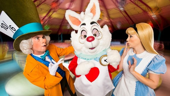Mad Hatter, Rabbit, and Alice in front of the Mad Tea Party attraction.