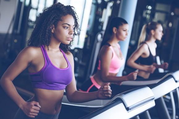 Women using running machines in a gym.