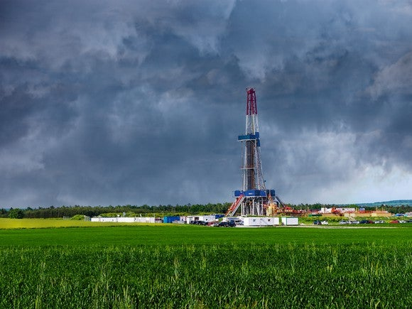 Drilling rig in field with clouds in background.