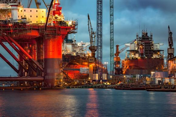 Multiple offshore rigs in a dockyard.