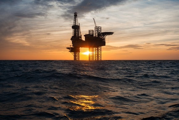An offshore drilling rig with the sun in the background.