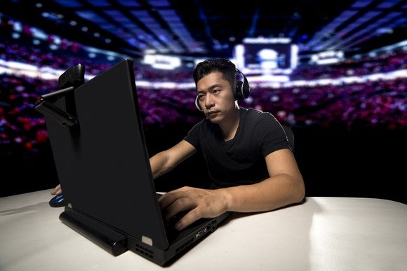 Young man wearing headphones and typing on a laptop.