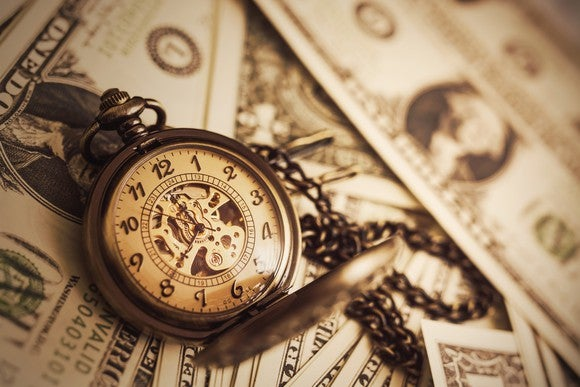 Old-style pocket watch with chain attached, sitting on top of dollar bills