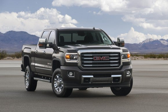 GMC truck sitting on an empty patch of concrete in a dry landscape.