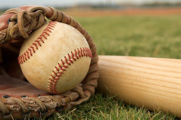 closeup of baseball in a glove and bat lying on the grass.