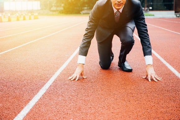 Suit-and-tie businessman kneeling on a running track, presumably at the starting line of a long race.