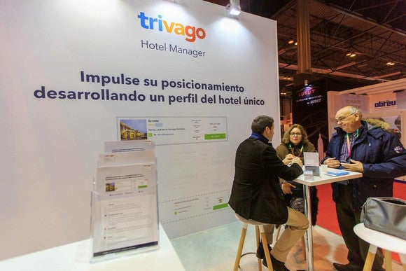 Three people at a table talking at an industry conference next to a sign for Trivago's hotel manager.