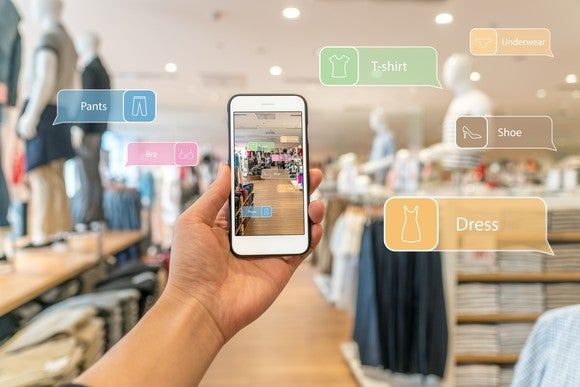 A hand holds a smartphone with an augmented reality (AR) shopping guide