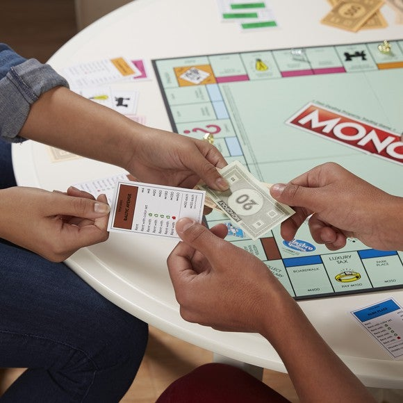 Two people playing the board game Monopoly.