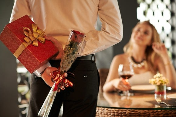 Man approaching a woman sitting at a table holding a rose and gift box behind his back