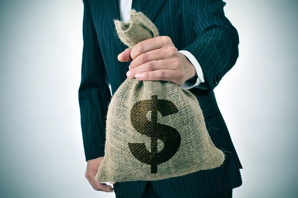 A man in a suit holds a burlap sack with a U.S. dollar sign emblazoned on it.