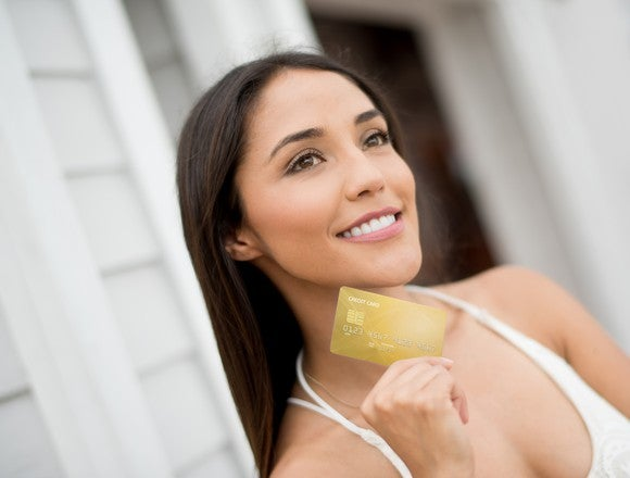 A young smiling woman holding a credit card.