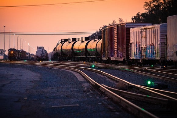 A freight train in a rail yard at dusk.