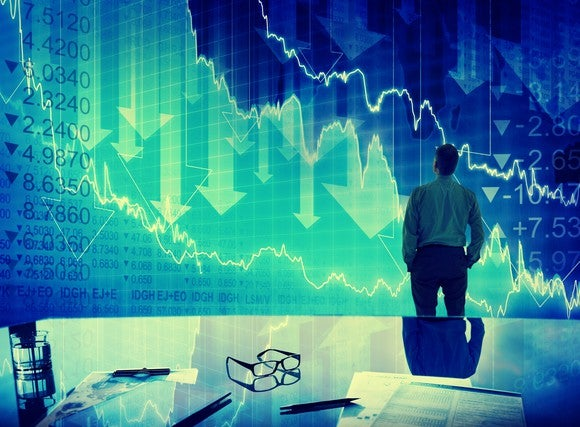 Man looking at stock prices and down arrows.