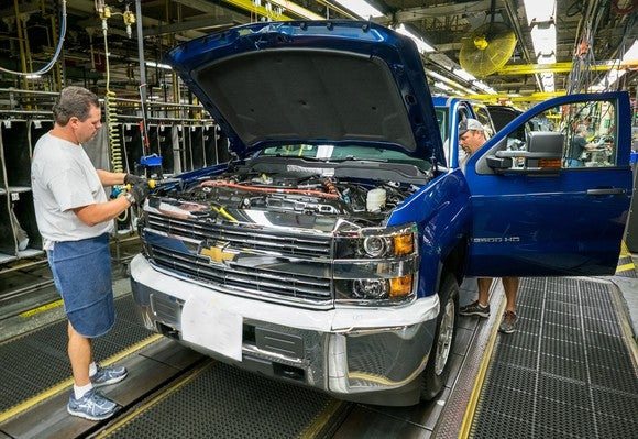 A blue Chevrolet Silverado 2500 HD is shown being attended by 2 workers on the assembly line at GM's Flint Assembly Plant in Flint, Michigan.