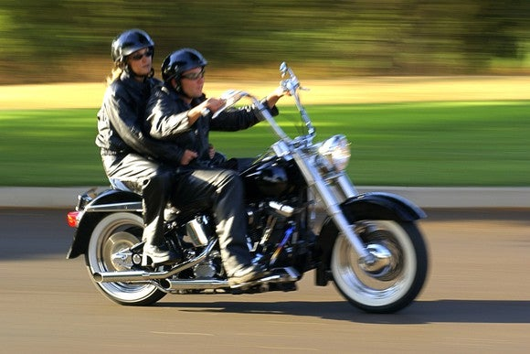Man and woman riding together on a motorcycle.