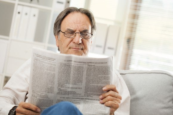Older man on a sofa, reading a newspaper