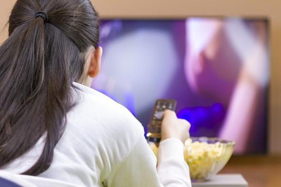 Woman watching TV eating popcorn