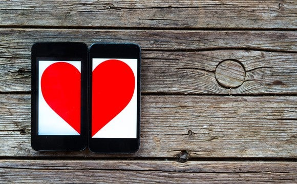 Two mobile phones with a heart displayed across both of them