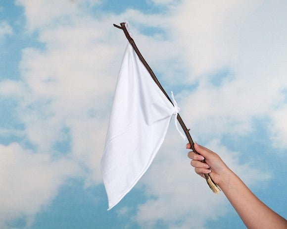 White flag at end of stick held by an arm against a partly cloudy sky.