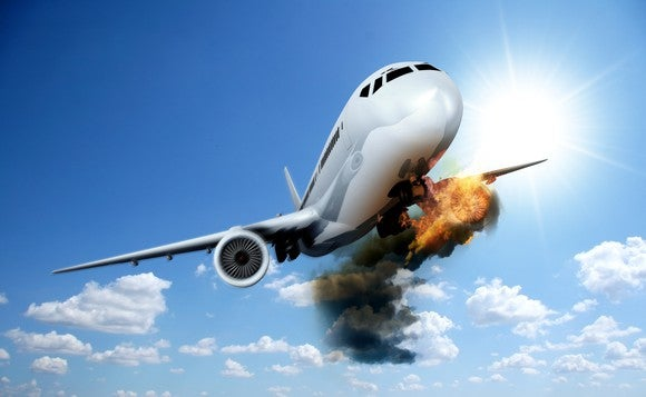 An airplane flying with an engine on fire.
