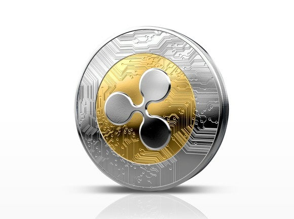 A physical coin with the Ripple logo on it.