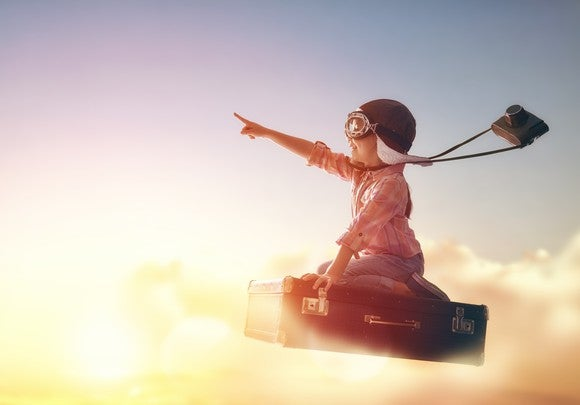 A rocket soaring into the sky with a little girl riding it who is pointing upward.