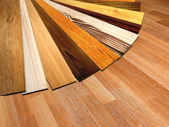 Various parquet wood flooring swatches in different colors fanned out on the floor.