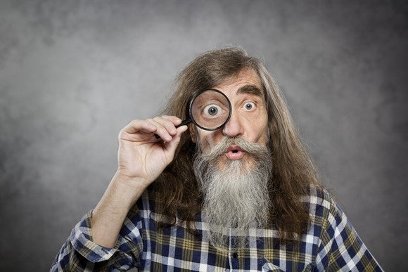 A man with a beard holding a magnifying glass to his eye.
