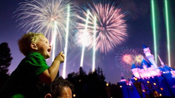 Young on the shoulder's on a man watching fireworks with a Disney Cinderella's Castle in background.