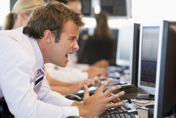 A frustrated stock trader in front of his computer screen.