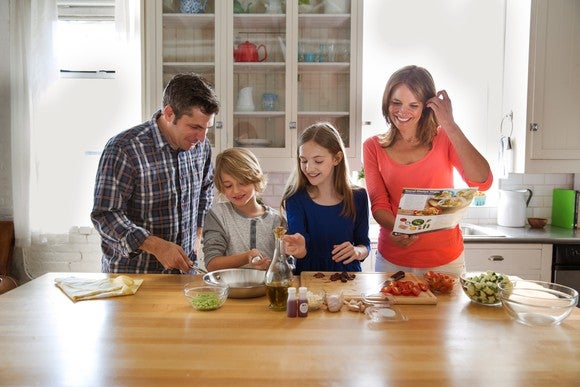 A smiling family of four preparing a Blue Apron meal kit, with bowls of different ingredients and an empty frying pan on a table in their kitchen.