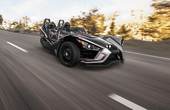 Polaris Industries Slingshot 3-wheel motorcycle racing down a tree-lined road