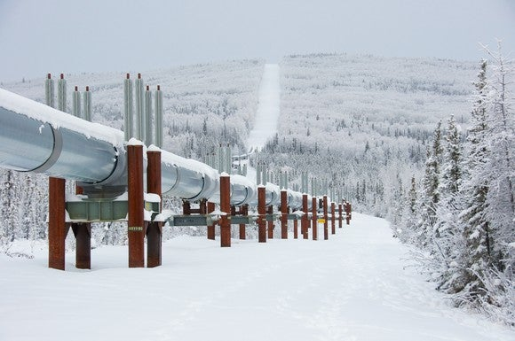A pipeline covered in snow forged through a forest.