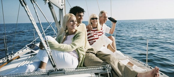 Four people smiling while sitting on a sailboat at sea.