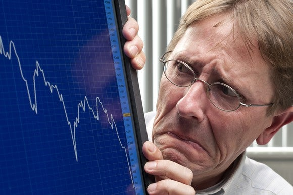 A terrified man looking at a plunging blue chart on his computer screen.