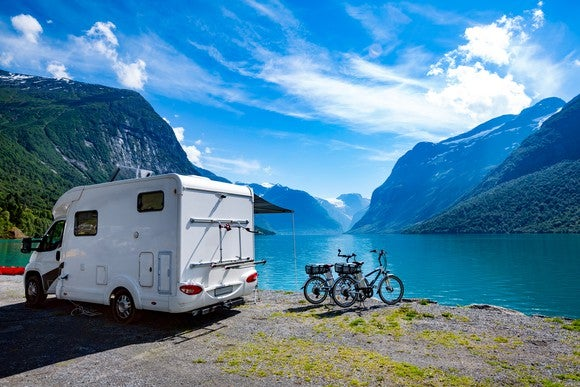 A white motorhome, with two bicycles next to it, parked next to a blue-green body of water and mountains in the background.